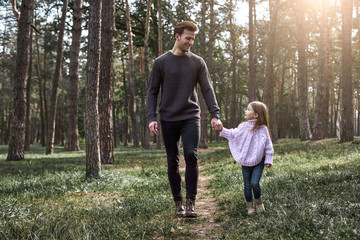 Father and daughter walking together in the forest. Full length