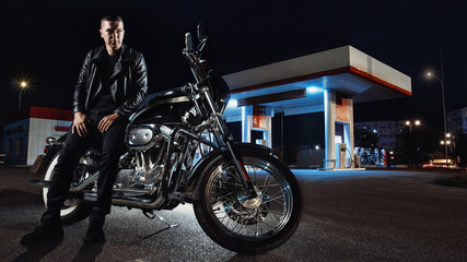 guy on a motorcycle looks into the distance the night city