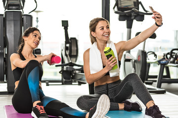Two cute girls taking a selfie photo while doing training at the gym