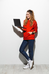Full length photo of cute woman 20s wearing red sweatshirt holding gray laptop, isolated over white background