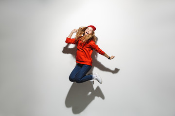 Full length photo of joyful woman 20s wearing red clothes laughing while jumping, isolated over white background