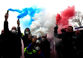 French ambulance drivers hold blue, white and red smoke bombs during a demonstration at the Place de la Concorde in Paris