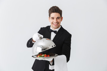 Portrait of a handsome young waiter in tuxedo