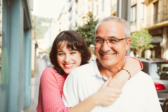 Portrait of happy father and daughter embracing on the street