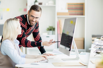 Cheerful hipster programming colleagues discussing app development: smiling handsome man giving advice to lady while pointing at monitor with script