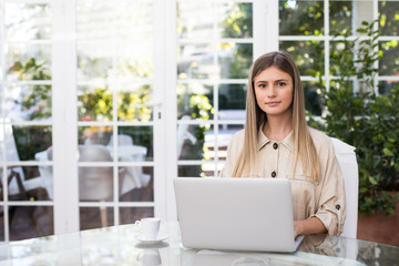 Attractive young woman in elegant outfit browsing laptop and looking at camera with serious face expression while sitting at table in stylish room