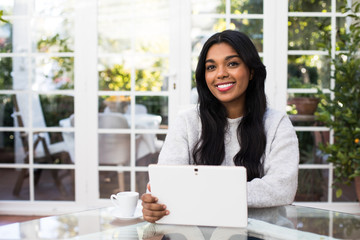 Pretty African American woman with modern tablet smiling and looking at camera while sitting at glass table in stylish room