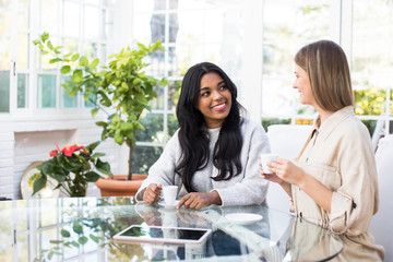 Two lovely young women smiling and looking at each other while enjoying hot drink at table in stylish room