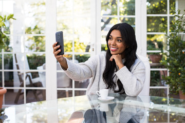 Pretty African American female smiling and taking selfie while sitting at glass table in stylish room