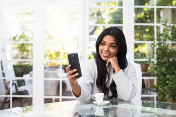 Attractive African American woman smiling and browsing modern smartphone while sitting at glass table in stylish room
