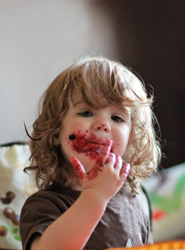 One year old baby girl eating delicious blueberry and black currant pie with her face dirty all over.