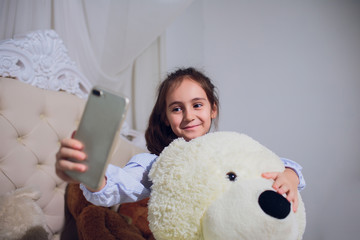 girl treats the bear and make selfie photo.