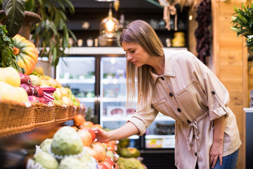 Side view of pretty young woman choosing fresh fruits in grocery store