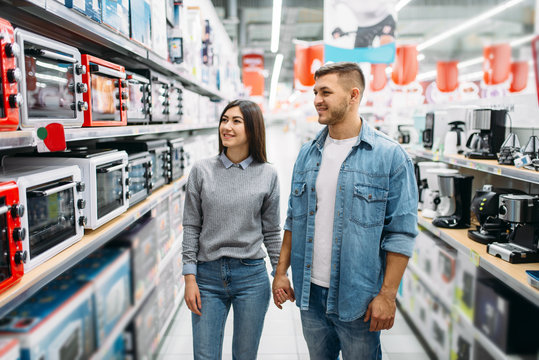 Couple looking on shelf with electric ovens