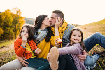 A portrait of young family with two small children in autumn nature at sunset, kissing.
