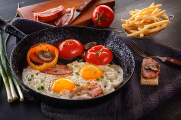 Fried eggs with bacon and tomatoes on an old cast-iron pan with french fries on a gray table. Close-up