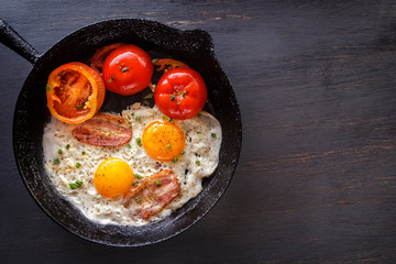 Fried eggs with bacon and tomatoes in an old cast-iron pan. Close-up. Top view
