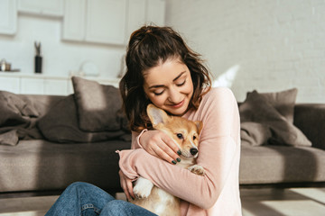beautiful woman embracing cute welsh corgi pembroke at home