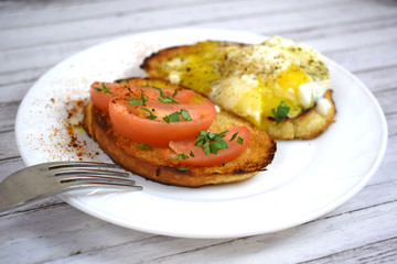 Crispy toast, scrambled eggs and tomatoes on a white plate for Breakfast.