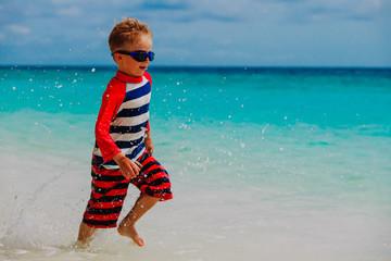 little boy run splashing water on beach