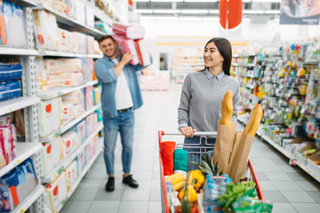 Couple buying a lot of diapers in supermarket