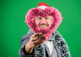 Man in love happy wear santa hat celebrate christmas green background. Spread love around. Merry christmas and happy new year. Hipster hold heart symbol of love. Bring love to family holiday