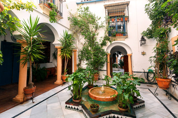 Traditional courtyard with columns, fountain and decor of Andalusia. Historical houses in Cordoba, Spain