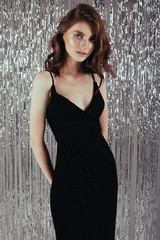portrait of graceful brunette woman with curly hair in trendy sequin dress looking at camera isolated over silver shiny background at christmas party. New year slyle fashion concept.