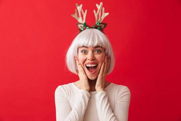 Pretty young girl wearing Christmas deer horns