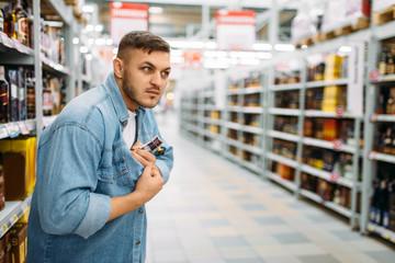 Man hides bottle of alcohol under his shirt