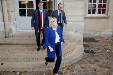French far-right National Rally (Rassemblement National) party leader Marine Le Pen and her companion Louis Aliot leave after a meeting at the Hotel Matignon in Paris