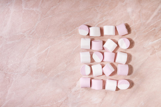 White pink big marshmallow in row over pink marble background. Flat lay, space. Sweet food and drink.