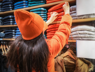 The girl holds out her hand for clothes on the store shelf. shopper pulls on a thing in a clothing store. Rear view of woman who holds out a hand to a shelf with clothes displayed in store.