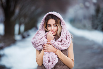 Winter portrait: Young pretty woman dressed in a warm woolen clothes, scarf and covered head posing outside.