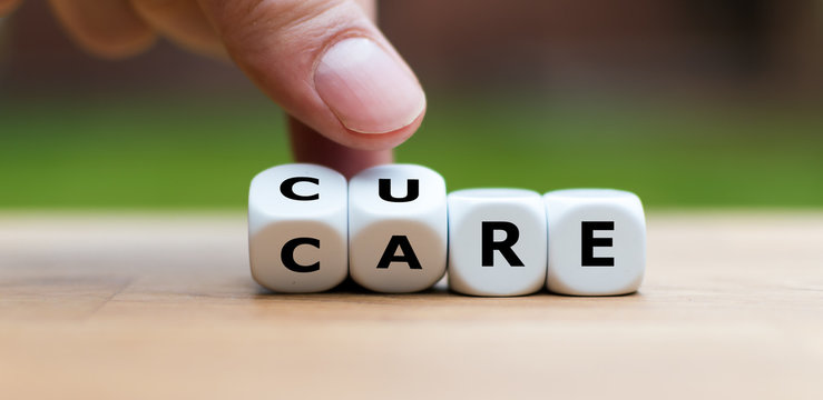 """Hand is turning dices and changes the word """"CARE"""" to """"CURE"""""""