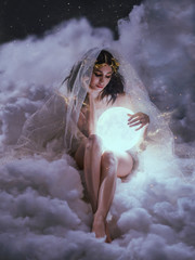 gorgeous slender sexy lady sits in the clouds and holds the moon in her hands. daughter of the sun and sky, keeper of dreams, ready to do good and a fairy tale under the cover of night and the stars