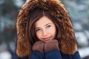 Winter portrait: Young pretty girl dressed in a warm woolen clothes, scarf and covered head posing outside.