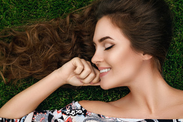 Beautiful woman with a healthy curly hair is lying on the grass