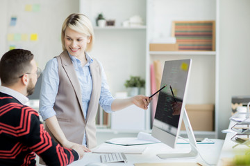 Cheerful confident pretty web designer with blond hair standing at table and pointing at computer monitor while presenting her project to manager in office