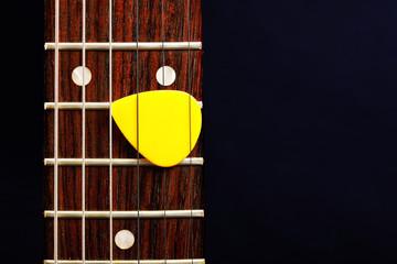 Guitar pick between strings
