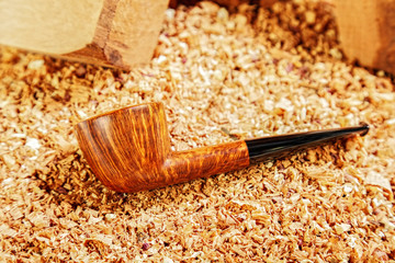 Smoking polished pipe and wood chips