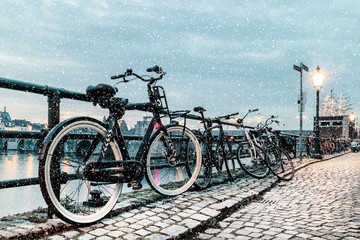 Winter view of parked bicycles alongside the Dutch river Maas