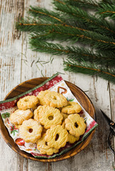 Christmas biscuits on wooden background. On the top thre are branches of fir.