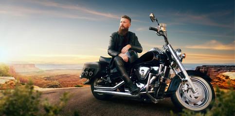 Biker sitting on his chopper and looks on sunset Fototapete
