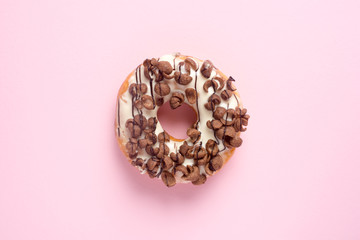 Fresh chocolate donut or doughnut decorated wit chocolate cereal on pink pastel table top