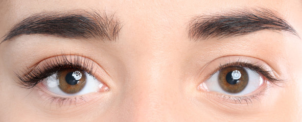 Closeup view of beautiful young woman before and after eyelash extension procedure