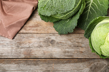 Flat lay composition with savoy cabbage and space for text on wooden background