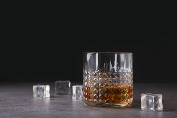Golden whiskey in glass with ice cubes on table. Space for text