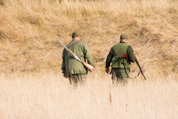 The hunter in the hunting clothes and with rifle hunts