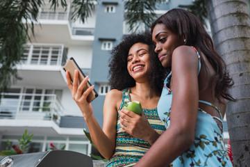 Cheerful black women using phone outdoors